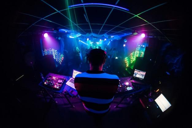 Dj mescola musica in un locale notturno con gente che balla