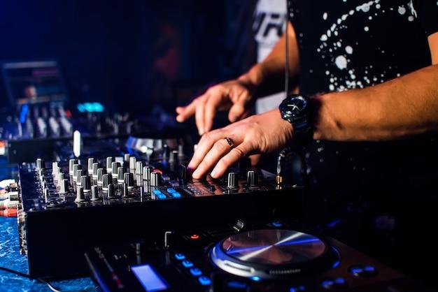 Dj mixa musica in un tabellone e attrezzature musicali professionali