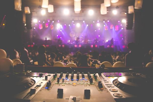 Dj spinning, mixing e scratching in un night club, luci stroboscopiche e nebbia