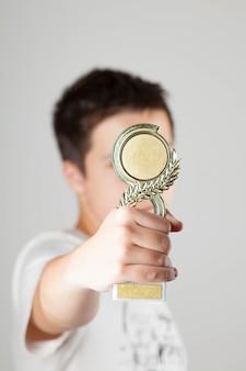 Dnepr, ucraina. giugno 2018. concetto di direzione. un adolescente tiene la tazza di un vincitore nelle sue mani, primo piano