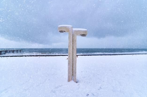 Doccia in spiaggia nel paesaggio invernale innevato