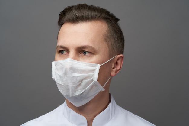 Doctor man indossa una maschera igienica per prevenire l'infezione.