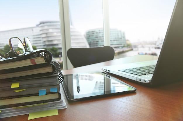 Documenti aziendali sulla tabella dell'ufficio con lo smart phone e la compressa digitale come affari dello spazio di lavoro.