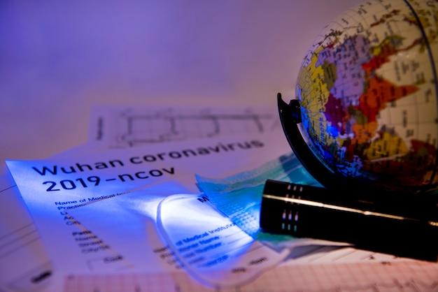 Documenti di medicina sotto la luce ultravioletta con sopra un piccolo globo