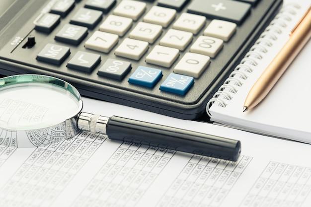 Documenti finanziari aziendali, calcolatrice ufficio e penna sul tavolo. numeri e grafici
