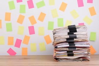 Documenti impilati sulla scrivania, carta colorata post-it sullo sfondo