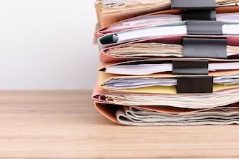Documenti impilati sulla scrivania.