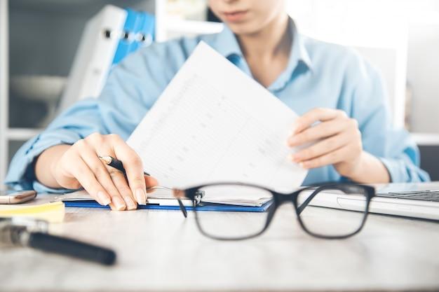Documento della mano della donna con gli occhiali sulla scrivania