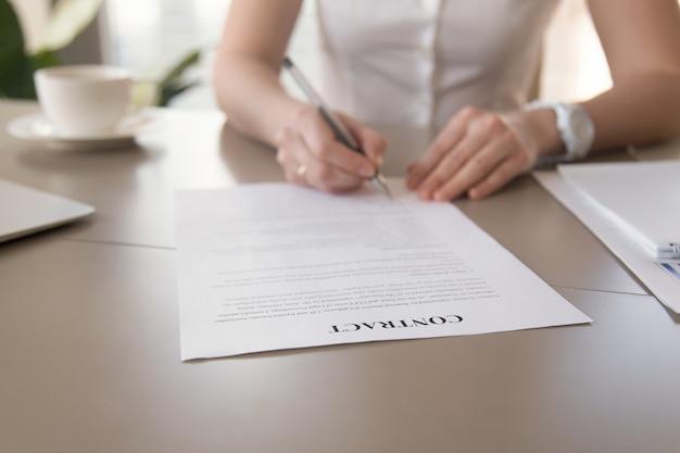 Documento di firma della donna di affari, mani femminili che mettono firma, fuoco sul contratto