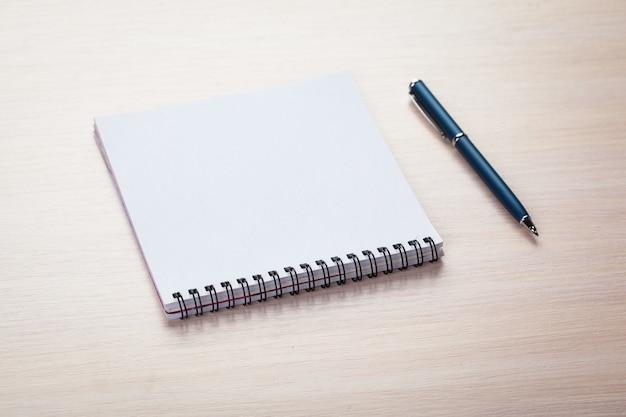 Documento di nota in bianco con la penna su legno
