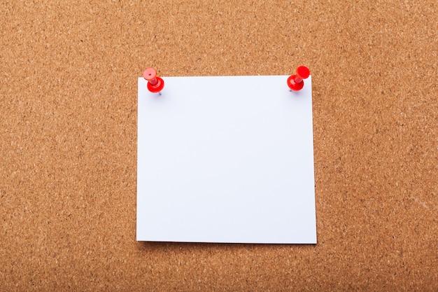 Documento di nota in bianco su una scheda del sughero