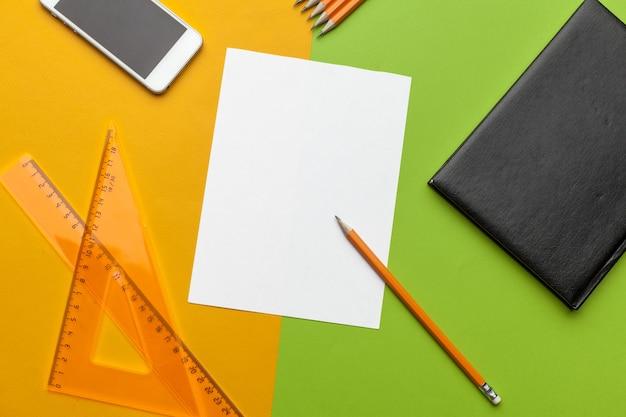 Documento in bianco con lo smart phone sullo scrittorio vista superiore, disposizione piana