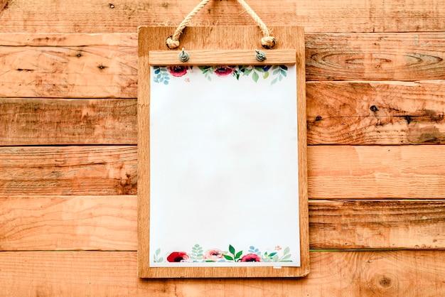 Documento in bianco su una lavagna per appunti per annunciare le notizie su una tavola di legno romantica di stile d'annata.
