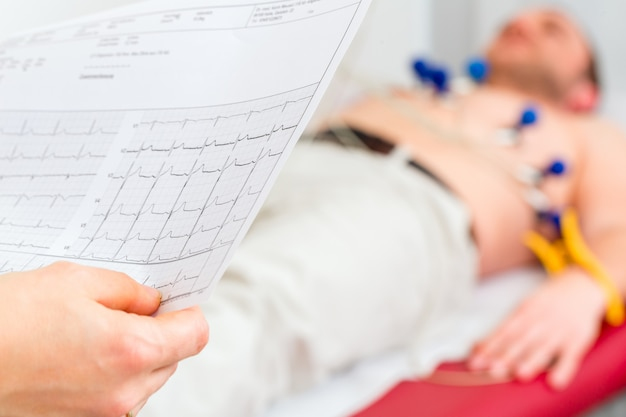 Doktor kontrolliert ekg paziente in arztpraxis