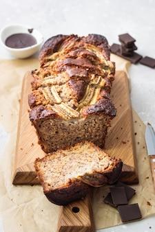Dolce alla banana o pagnotta con cioccolato su un tagliere di legno