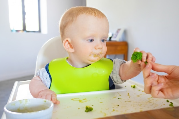 Dolce bambino in bavaglino prendendo broccoli pezzo dalla mamma