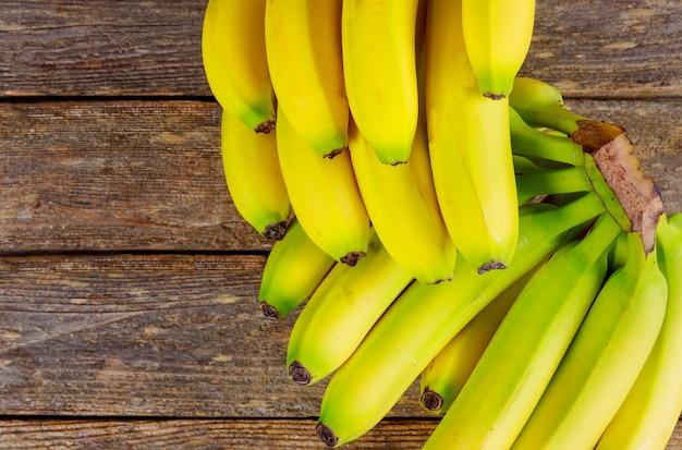 Dolce banane mature su un tavolo di legno.