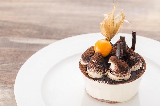 Dolce del dessert di tiramisù con il primo piano a terra della ciliegia sul piatto bianco e sulla tavola di legno