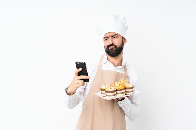 Dolce del muffin della tenuta del giovane che pensa e che invia un messaggio