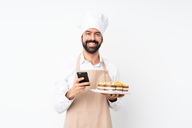 Dolce del muffin della tenuta del giovane sopra la parete bianca isolata che invia un messaggio con il cellulare