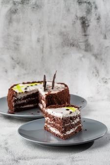 Dolce di cioccolato delizioso con la crema bianca della noce di cocco sul piatto sulla tavola su fondo di marmo. carta da parati per pasticceria o menu bar. verticale.