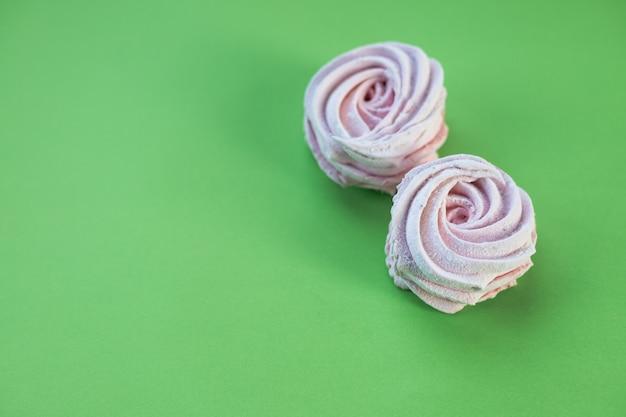 Dolce di zefiro della caramella gommosa e molle della meringa del dessert di recente del primo piano isolato sulla parete verde. dessert di caramelle.