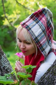 Dolce donna con cappuccio nella foresta, odorando il ricco aroma di un bellissimo fiore rosa.