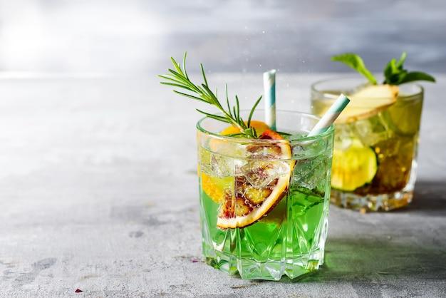 Dolce liquore alla menta rinfrescante, con ghiaccio, mandarino rosso e rosmarino su tavolo in pietra concreta grigia