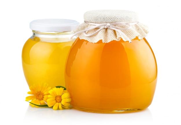 Dolce miele in barattoli di vetro con fiori isolati su bianco