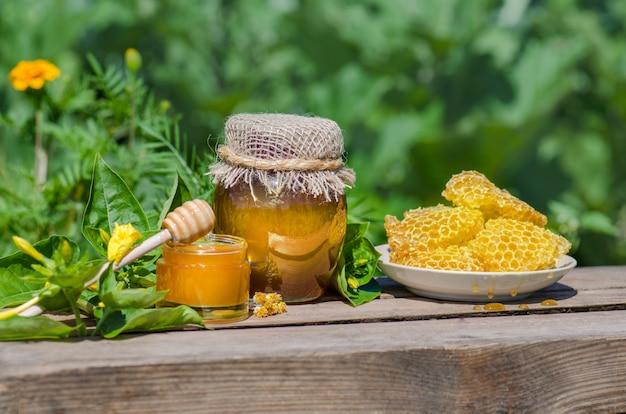 Dolce miele nel pettine. vasetti di miele, ape a nido d'ape sul tavolo di legno con fiori