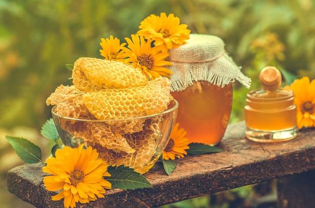 Dolce miele, pezzi di pettini e mestolo di miele. miele gocciolante da mestolo di miele e fiori primaverili. vita di campagna ucraina