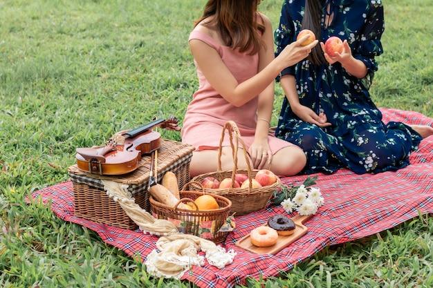 Dolce momento d'amore. ritratto di coppia omosessuale asiatica che gioca con il violino e pic-nic nel parco. concetto lgbt leasbian.