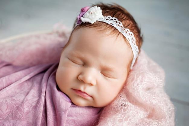 Dolce neonato che dorme. ragazza neonata di 3 settimane che giace in un cesto con plaid in maglia. ritratto di ragazza appena nata. immagine del primo piano