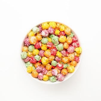 Dolce popcorn giallo, viola, verde, arancione e rosso in una ciotola su un tavolo bianco.