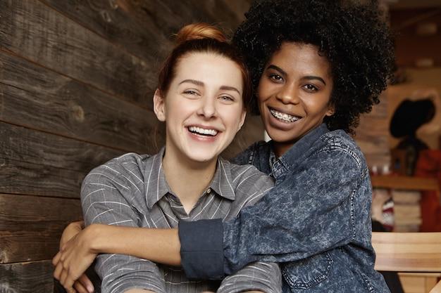 Dolce scatto di felice coppia gay interrazziale che si gode il loro amore libero, coccolandosi e abbracciandosi