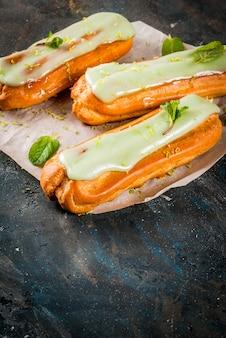 Dolce tradizionale francese. mojito eclairs con scorza di lime e foglie di menta, su blu scuro, copyspace
