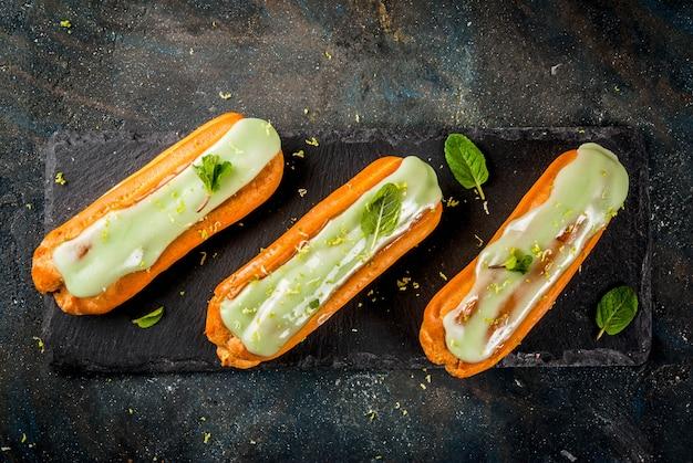 Dolce tradizionale francese. mojito eclairs con scorza di lime e foglie di menta, su blu scuro, vista superiore del copyspace