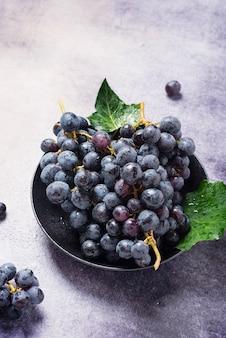 Dolce uva nera fresca sul tavolo scuro