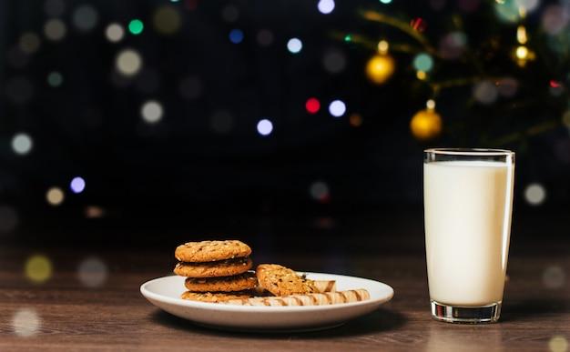 Dolcetti di natale e del bicchiere di latte su un piatto