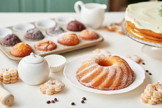 Dolcetti di natale sul tavolo: cupcake, torta nuda, biscotti e caffè con miele