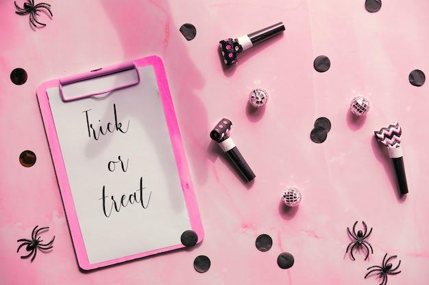 Dolcetto o scherzetto il testo sul blocco degli appunti su sfondo rosa. decorazioni per feste: coriandoli di carta, rumori, ragni di plastica nera.