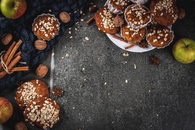 Dolci autunnali invernali. cibo vegano. sano biscotti da forno fatti in casa, muffin con noci, mele, fiocchi d'avena. atmosfera casalinga accogliente, coperta calda, ingredienti. tavolo in pietra scura. copia spazio vista dall'alto