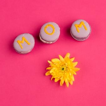 Dolci biscotti viola con titolo mamma vicino ai boccioli di fiori