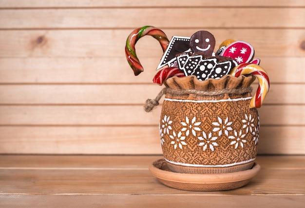 Dolci, caramelle e pan di zenzero in vaso di terracotta sul tavolo di legno.