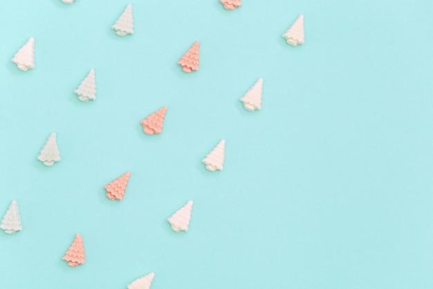 Dolci caramelle pastello carino pastello vista dall'alto di natale o capodanno, a forma di alberi di natale si trovano nelle file.