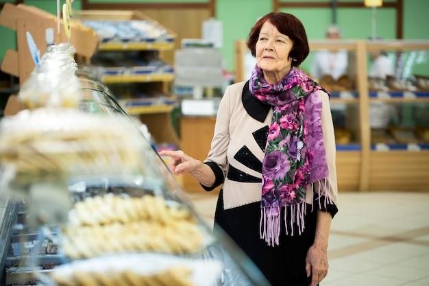 Dolci d'acquisto della donna al supermercato