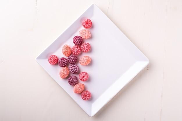 Dolci dei bastoncini di zucchero nella forma di bacche succose sul piatto bianco su fondo bianco isolato, vista superiore