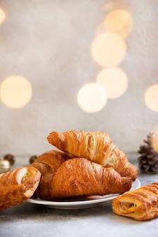 Dolci di natale o capodanno, cornetti al cioccolato e mela. atmosfera natalizia. concetto di vacanze invernali. sfondo chiaro. messa a fuoco selettiva