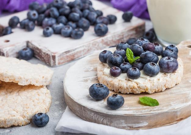 Dolci di riso biologici sani con ricotta e mirtilli freschi su tavola di legno e bicchiere di latte