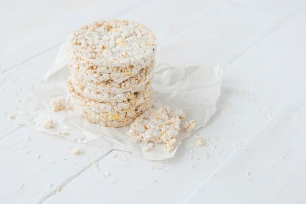 Dolci di riso soffiati rotti e rotondi sulla tavola di legno bianca